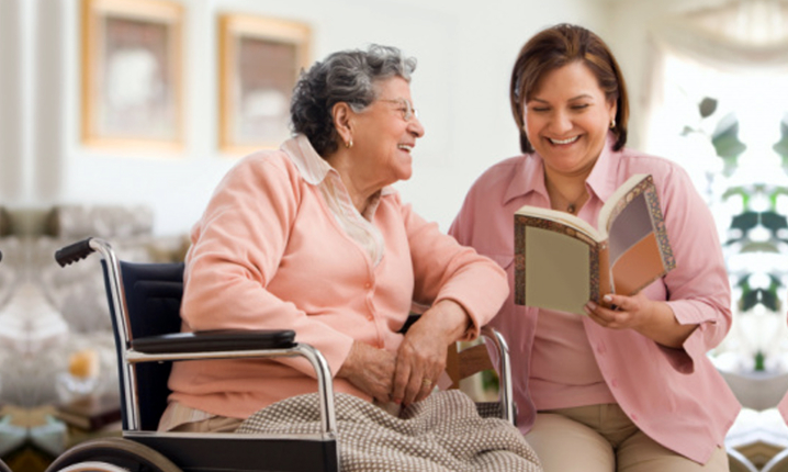 caregiver reading book to senior woman