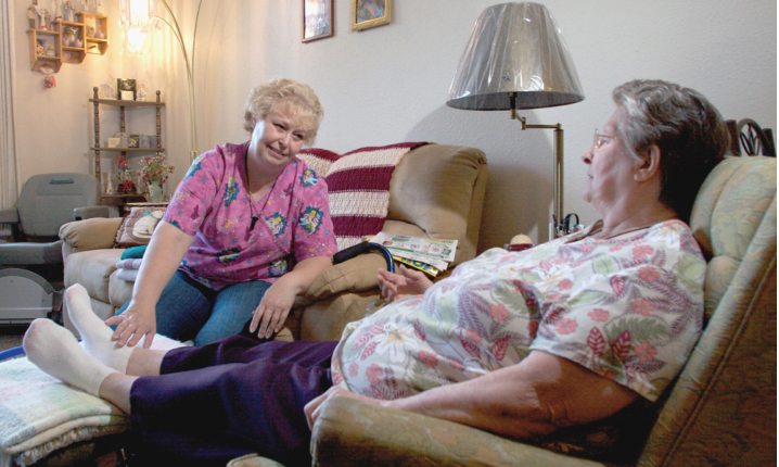caregiver massaging feet ti senior woman